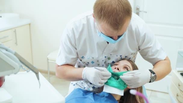 Lékař v rukavicích léčí dívce zuby k pacientovi. Kontrola u zubaře pomocí zrcadla.