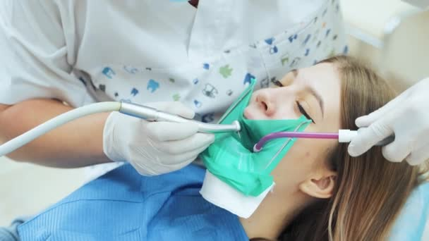 Zubař s vrtačkou léčí zub pacientce na zubní klinice..