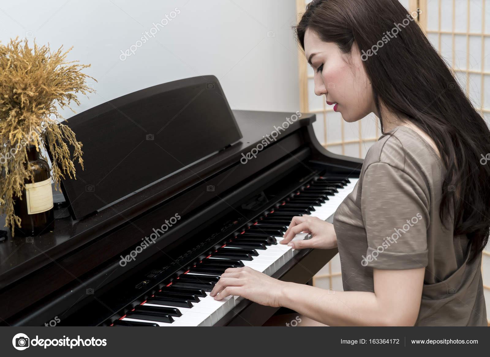 junge musiker frau spielt klavier im wohnzimmer stockfoto pixs4u 163364172. Black Bedroom Furniture Sets. Home Design Ideas