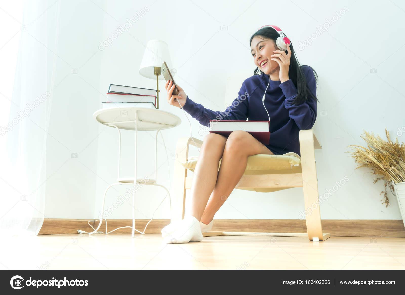 Moderne Muziek Woonkamer : Aziatische tiener hoofdtelefoon dragen in moderne woonkamer