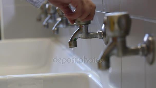 mano di apertura molti rubinetti di acqua in bagno scuola — Video ...