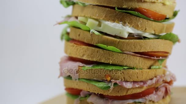 gant sandwich stuffed with many layers of bread with lettuce tomato cheese salami