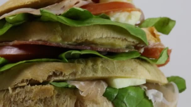 gant sandwich stuffed with layers of bread with tomato cheese salami