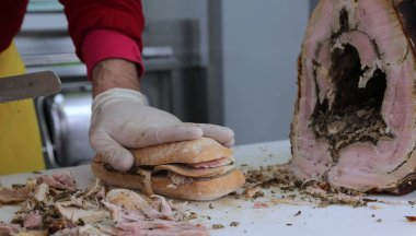 slicing the meat of pork to prepare a sandwich in the food stall