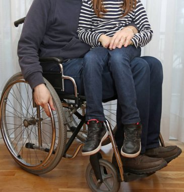 disabled parent in a wheelchair with his little daughter