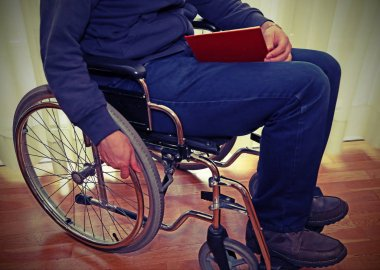 man in a wheelchair reading a book with vintage effect