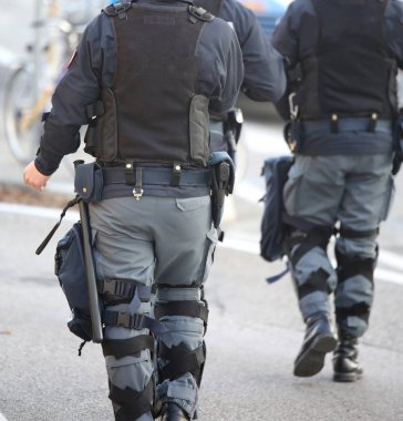 two anti-riot police cops patrol the streets of the