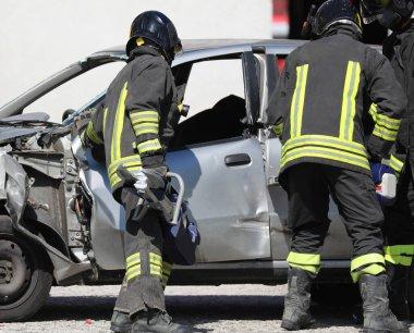 İtfaiyecilerden oluşan bir ekip hasarlı arabayı açar.
