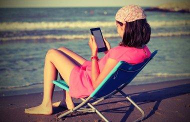 little girl reads the ebook on the beach