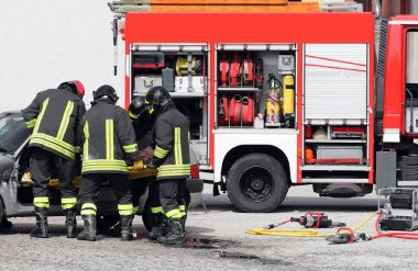 fire truck and firefighters with the stretcher extract the injured from the car after the road accident