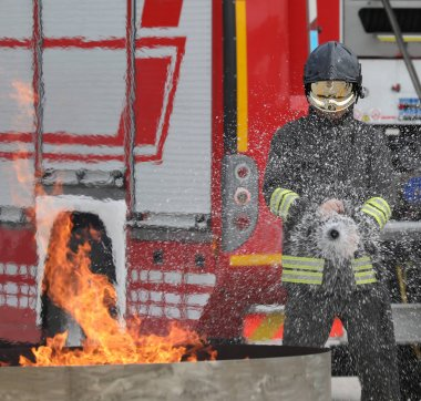brave fireman with helmet during the extinguishing of a fire during the practical training test