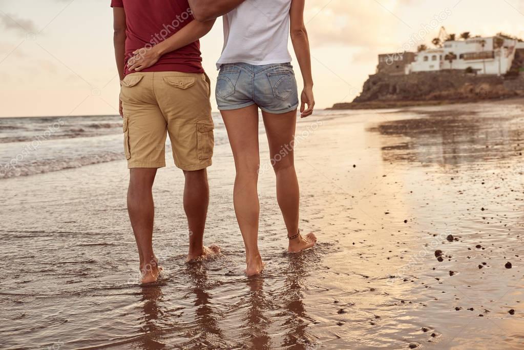 Lovers strolling through breaking waves