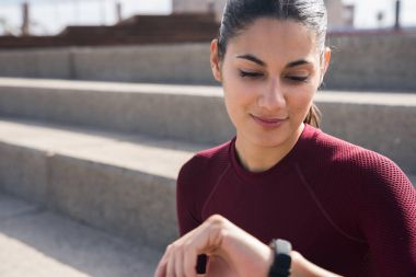 Young pretty woman looking at smartwatch