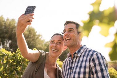 A man and woman taking a selfie in the vineyards smiling broadely at the phone camera stock vector
