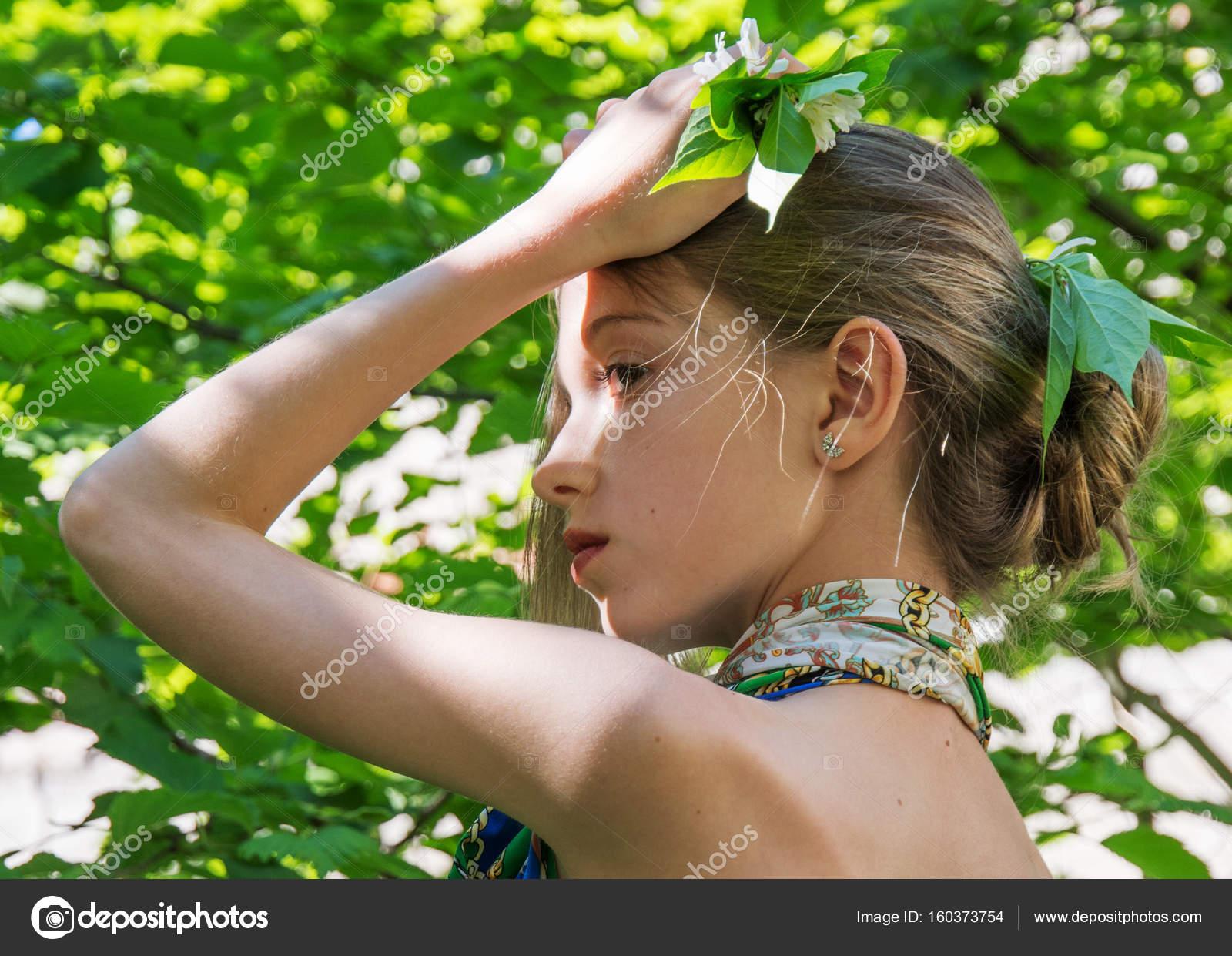 Ein junges Mädchen in einem Kleid mit nackten Rücken einen
