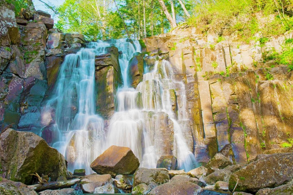 beautiful forest waterfall. on the stony slope runs stormy forest waterfall.