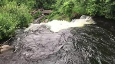 Beautiful view on top of a waterfall park during a hot summer day. People visit nature landscape and hiking trails walking over stone bridge down below river