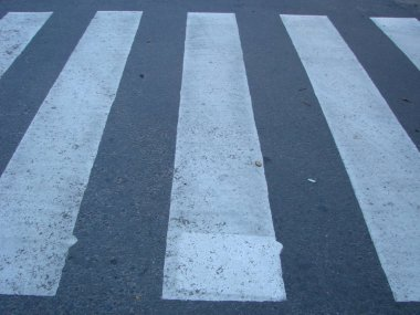 crosswalk on the road for safety when people walking cross the street.