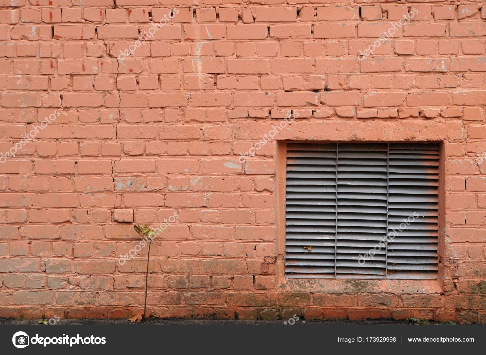 Gut Die Wand Besteht Aus Ziegeln. Es Ist Mit Orange Farbe Gemalt. Hintergrund.  Von Außen. Technologische Fenster Mit Einem Gitter.