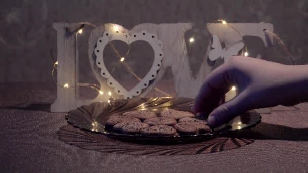 Ženská ruka přijímá soubory cookie. Sušenky ve tvaru srdce. Temná atmosféra. Nápis Love ze dřeva. Věnec z malých cibulí. Den svatého Valentýna. Romantickou atmosféru. Designový prvek
