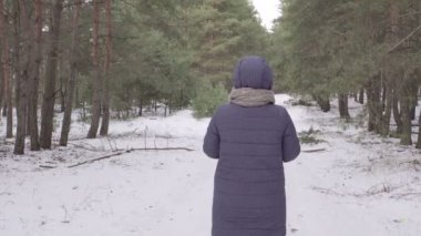 The girl goes on a snowy road. Tall trees in the woods. Blue jacket. The green branches. The tourist and traveler. 4K video