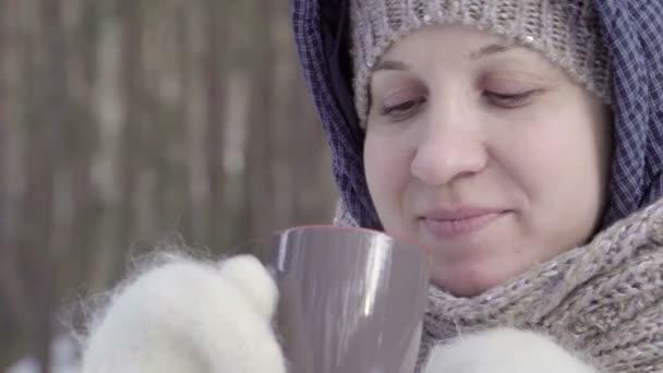 Dívka v bílé rukavice, pití z tmavé hrnek. Big shot. Šála a čepice pod kapotou. Modré sako. Zimní les. Rozmazané pozadí. Turistické a cestovatel. 4k video