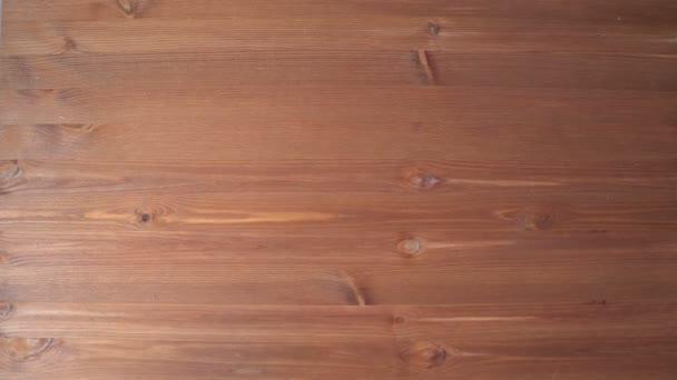 Ruka je kus bílého papíru na stole. Tmavý dřevěný stůl. Střípky z těla. Ruka s rukávy. Texturu dřeva. Pohled shora. Country styl. 4k video