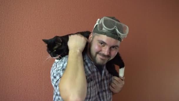 Ein Mann hält die dunkle Katze auf seinen Schultern. Kuscheltier. Streicheln des Fells mit der Hand. im karierten Hemd. die grüne Kappe. Schutzbrille auf dem Kopf. 4k-Video