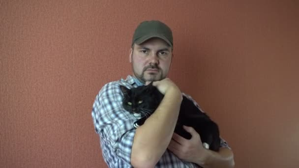 Ein Mann hält in den Händen der dunklen a. flauschige Tier. Das Fell mit der Hand streicheln. In einem karierten Hemd. Die grüne Kappe. Ruhig ernstem Gesicht. 4k video
