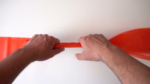 Orange ribbon sul tavolo. Due mani si estendono expander. Close-up. La vista dallalto. Un frammento del corpo umano. Attrezzature sportive. Azione fisica. Tavolo grigio. video 4K