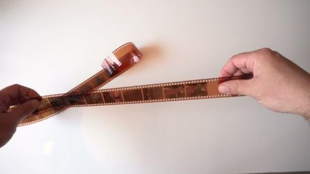 Mostra vecchia pellicola fotografica. Piccole cornici. Mani depilato il nastro. Lampada da tavolo. La vista dallalto. video 4K