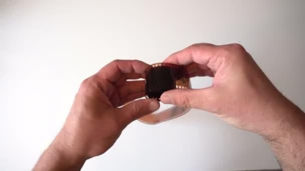Verdrehung des alten Films. Kleine Rahmen. Hände zupften am Band. Leuchttisch. Vintage-Objekt. die Aussicht von oben. 4k-Video