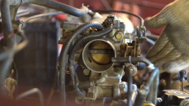 Automechanik kontroluje vzduchový ventil. Detail na autě. Vesmír Hooda. Detailní záběr. Autoservis. Analyzujte auta. Náhradní díly. Oprava auta. Ladění motoru.