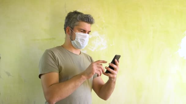 An adult man is standing against the wall. There is a medical mask on the face. Holds a smartphone in his hand. Phones on the phone. Virus protection. Business. The crisis. Money.