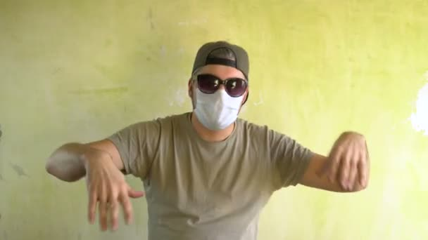 Adult man with glasses. There is a medical mask on the face. Dancing against the wall. Virus protection. Military defense. A builder at a construction site.