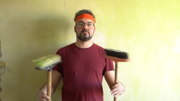 Legrační muž s vousy změní sexuální štětec. Stojí u zdi