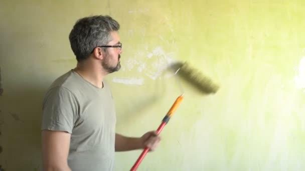 Ein bärtiger Mann bemalt eine Wand. Gute Laune. Ein Lächeln auf seinem Gesicht. Reparaturarbeiten im Raum. Schauspieler. Frick. Clown.