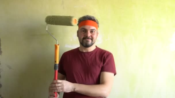 Bärtiger Mann gegen die Wand. Gute Laune. In den Händen einer Bauwalze für die Malerei. Die Performance des Künstlers. Musikalische Nummer. Auf dem Kopf befindet sich ein orangefarbenes Band. Reparaturarbeiten im Raum. Frick. Retro-Stil. Grüne Mauer.