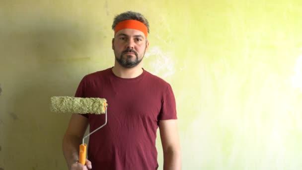 Ein bärtiger Mann steht an der Wand. In der Hand liegt die Rolle. Auf dem Kopf befindet sich ein orangefarbenes Band. Reparaturarbeiten im Raum. Frick. Retro-Stil. Grüne Mauer.