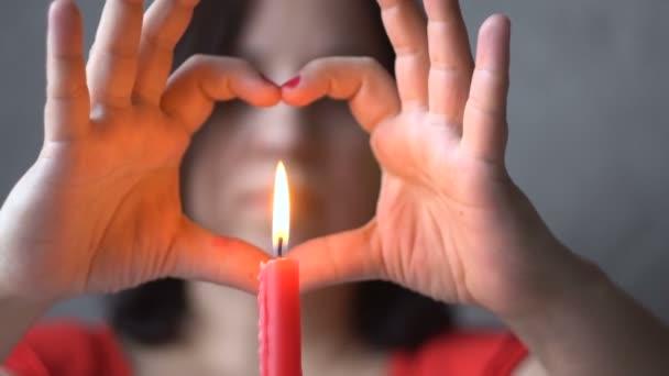 U stolu sedí mladá žena. Hořící svíčky Ruce v podobě srdce. Symbol lásky. Sv. Valentýna. Dovolená. Vyjádření lásky. Detailní záběr.