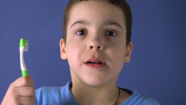Chlapec stojí s kartáčkem na zuby. Ukazuje zuby. Věk 6 let. Vtipný, vtipný pohled. Detailní záběr portrétu.