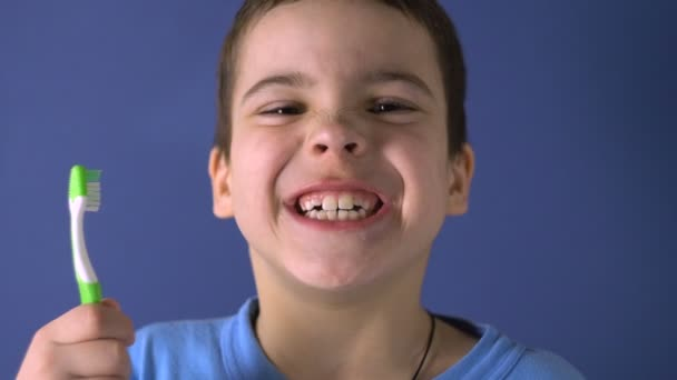 A boy is standing with a toothbrush. Shows teeth. Age 6 years. Funny, funny look. Close-up portrait.