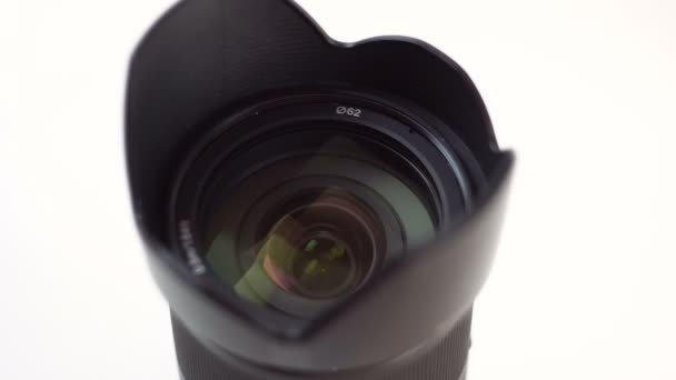Černá fotografická čočka se otáčí. Vybaven ochranou proti oslnění. Bílé pozadí. Makro. Detailní záběr. Úlomek objektu..
