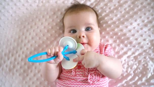 A kislány egy rózsaszín takarón fekszik. Öt hónapos. Színes játékot tart a kezében. Csíkos ruha. Európai típusú arc. Kilátás fentről. Közelkép.