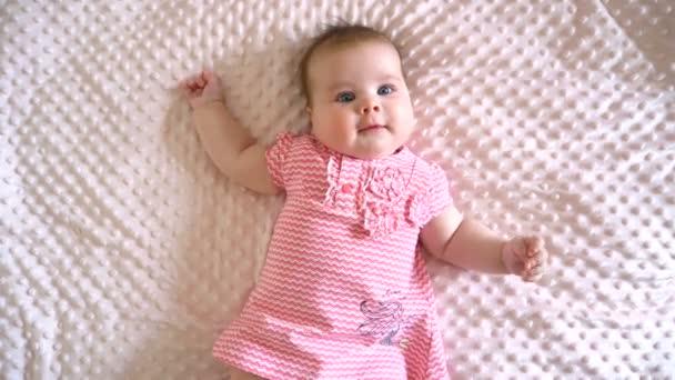 Holčička leží na růžové dece. Věk 5 měsíců. Proužkované šaty. Obličej evropského typu. Pohled shora. Detailní záběr.