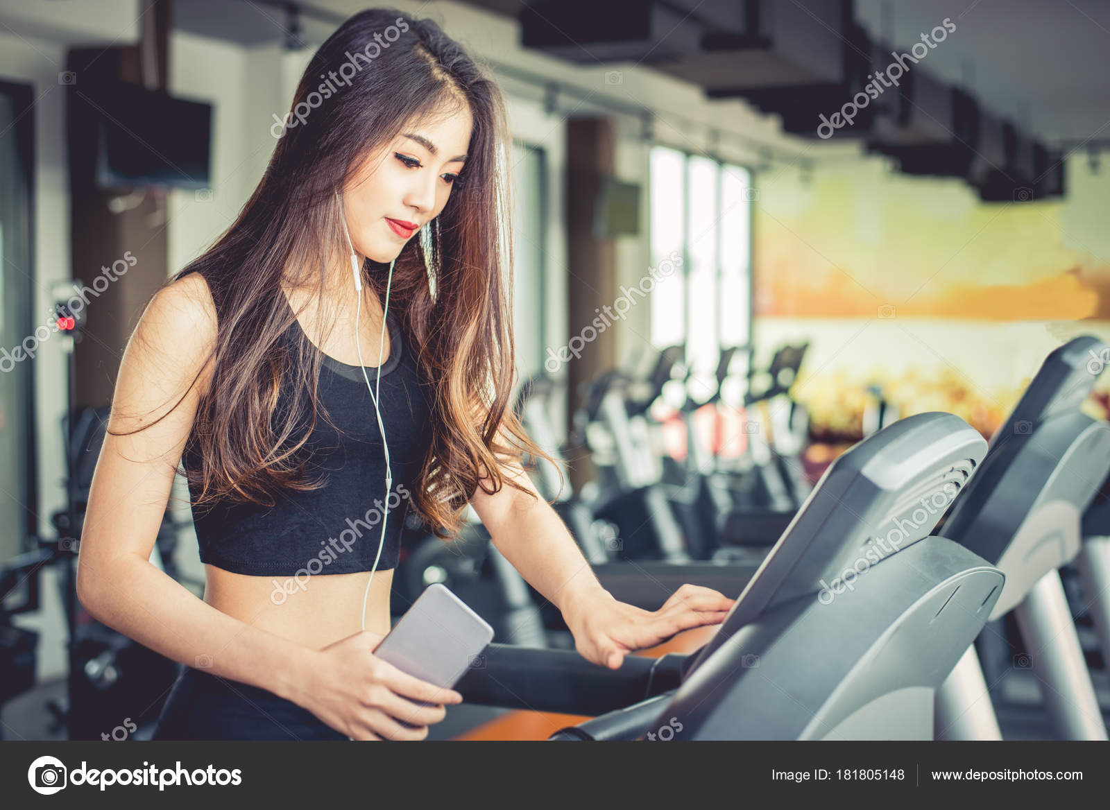 b2a47bb959d Asian woman using smart phone when workout or strength training at fitness  gym on treadmill.