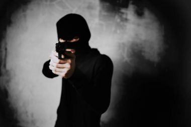 Terrorist shooting with his mini gun weapon in abandoned building background. Criminal and Dangerous illegal people concept. Terrorist and war theme. Dark tone and high contrast use.