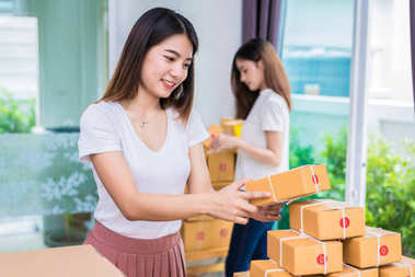 Two young Asian girl freelancers business owner working at home office and sorting parcel post box to delivery service to customer. Packaging order and Shopping online concept.