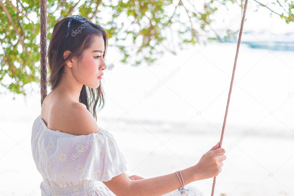 Asian woman on white dress sitting on swing at beach. People and Nature concept. Sad love and Missing someone concept. Lonely and Heart broken theme.