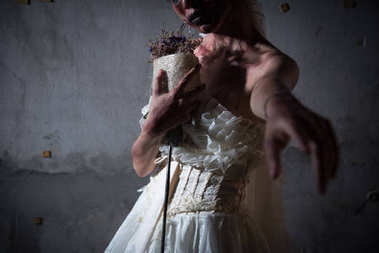 Bride Zombie in wedding dress with dried flowers pointing and want you to stay with her in abandoned house, Halloween theme, Ghost and deadman concept, Heart broken and neglected concept, Dark tone